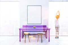 Woman Minimalism purple table dining room, poster. Woman in a white minimalism dining room interior with loft windows, a purple table, chairs and a bench. A Stock Image