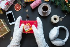 Woman in white mittens makes gifts for New Year and Christmas with cup of coffee royalty free stock photography