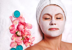Woman with white mud mask. Woman enjoying spa with facial mud mask and rose petals Royalty Free Stock Photos