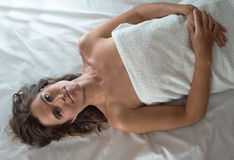 Woman on white muffled white towel Royalty Free Stock Image