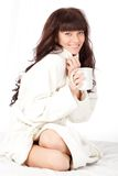 Woman with white mug wearing dressing gown Royalty Free Stock Images