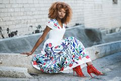 Woman in White and Multicolored Floral Flare Dress Sitting on Concrete Stock Photography