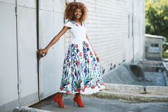 Woman in White and Multicolored Midi Dress Holding Door Stock Photography