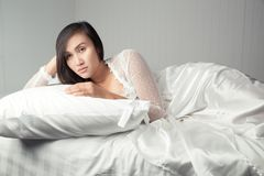 Woman in white nightgown Can`t Sleep. Asian woman in white satin nightgown lying in bed suffering from insomnia, Not sleeping, Lady stressed because of too early Stock Photos