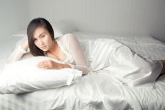Woman in white nightgown Can`t Sleep. Asian woman in white satin nightgown lying in bed suffering from insomnia, Not sleeping, Lady stressed because of too early Royalty Free Stock Images