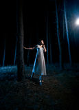 Woman in white nightgown looking at beam of light at night fores Royalty Free Stock Photos