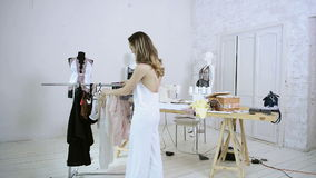Woman in white nightie comes to rack with hangers to choose clothes. In light room. Blonde lady in white clothe moving hanger, take lace transparent shirt stock video footage