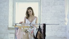 Woman in white nightie comes to rack with hangers to choose underwear. Cute nice brown-haired lady in white dress moving hanger, choosing black sexy lace stock footage