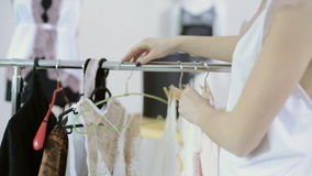 Woman in white nightie comes to rack with hangers to choose underwear. In light room. Close up shooting hands of lady in white dress moving hanger, choosing stock video footage