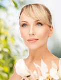 Woman with white orchid flower Royalty Free Stock Images