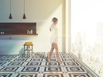 Woman in white panoramic bathroom interior. Woman in a stylish bathroom interior with white walls, tiled floor, a white bathtub and a black shelf with shampoo stock photography