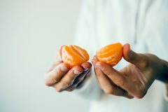 Woman in white pullover holding half of mandarin in hands. Closeup. Love and share concept. Atmosphere and mood picture Royalty Free Stock Images