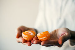 Woman in white pullover holding half of mandarin in hands. Closeup. Love and share concept. Atmosphere and mood picture Royalty Free Stock Photography
