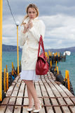 Woman in white with red bag sea footbridge Royalty Free Stock Photo
