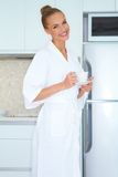 Woman in white robe drinking coffee Royalty Free Stock Image