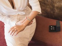 Woman in white robe and lace underwear. Wedding concept. Woman in a white robe and lace underwear puts the bracelet on her arm. On a woman`s finger - ring with Stock Image