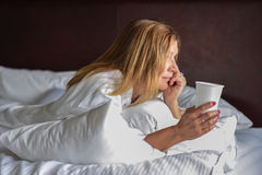 Woman in white robe laying on bed in morning with cup of coffee Royalty Free Stock Photo