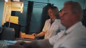 Woman in white robe manage orange plastic trays in laboratory. Caucasian woman in white robe manage orange plastic trays in laboratory gray haired man in glasses stock video