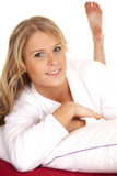 Woman white robe red sheet lay looking Royalty Free Stock Image