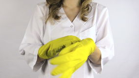 Woman in white robe smock put on yellow rubber gloves on hands Royalty Free Stock Photo