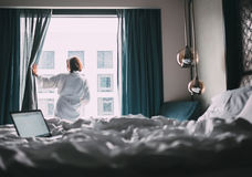 Woman in white robe stay hear the window in hotel room Stock Photo