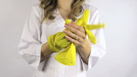 Woman in white robe  take yellow rubber gloves off her hands stock video footage
