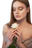 Woman with white rose in her hands looking down Royalty Free Stock Image