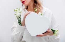 Woman with white roses holding a heart shape gift box. stock image