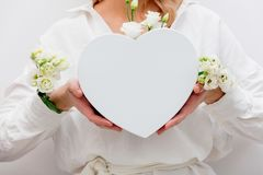 Woman with white roses holding a heart shape gift box. stock photo