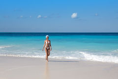 The woman in white sexual bikini goes on a peschenny beach against turquoise ocean Stock Photo