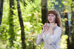 The woman in a white shirt against foliage Royalty Free Stock Photos