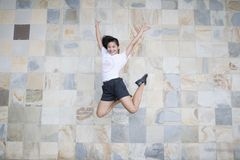 Woman in White Shirt and Black Shorts Taking Jump Shot Near Wall royalty free stock photo