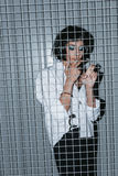 Woman in white shirt and cuffs smoking cigarette behind grate Royalty Free Stock Images