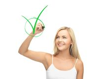Woman in white shirt drawing green checkmark. Smiling woman in white shirt drawing green checkmark Stock Photos
