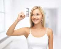 Woman in white shirt drawing red checkmark Royalty Free Stock Image