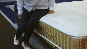 A woman in a white shirt examines the mattress, she squats and and sits down at the mattress. In a mattress store stock video footage
