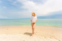 Woman in white shirt and hat posing on sandy beach at sunny day Royalty Free Stock Images