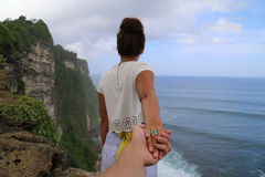 Woman in White Shirt Holding Hand With Other Person on Top of the Island Overlook Blue Ocean Under White and Blue Sky Royalty Free Stock Image