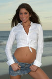 Woman in White Shirt and Jean Skirt Tugging on Belt Loops. Beautiful Young Brunette Woman in White Shirt and Jean Skirt Tugging on Belt Loops Stock Photos
