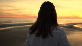 Woman In White Shirt And Jeans Looks At The Sea. Rear View Unidentified Young Woman In White Shirt And Jeans Looks At The Sea During Sunset Warm Summer Day stock video