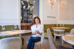 Woman watching mobile smartphone in restaurant Royalty Free Stock Image