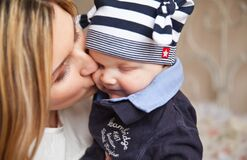 Woman in White Shirt Kissing Baby With Black and White Stripe Knit Cap Royalty Free Stock Photography