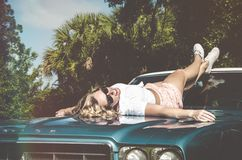 Woman in White Shirt Laying on Green Car Hood Stock Photography