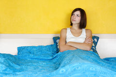 Woman in white shirt sitting alone on double bed Stock Photo