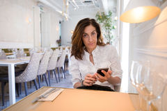 Woman using mobile phone in restaurant looking Stock Images