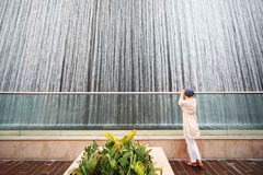 Woman in white shirt standing near big fountain Stock Photos