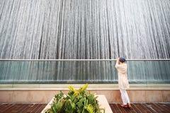 Woman in white shirt standing near big fountain Stock Photos