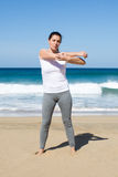 Woman in white shirt stretches her arms on beach Stock Photos