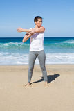 Woman in white shirt stretches her arms on beach Royalty Free Stock Image