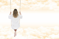 Woman with white shirt on the swing through the clouds of an amb. Blonde woman thoughtful and relaxed, back view, dressed in white shirt for men, on the swing Stock Photo